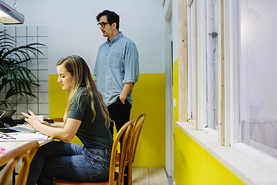 Young woman and man in board room at creative office - p426m1407162 by Maskot
