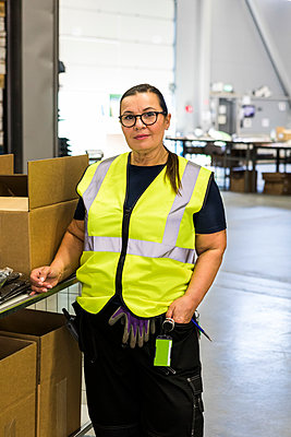 Portrait of confident mature female worker standing by cart in distribution warehouse - p426m2018867 by Maskot