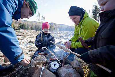 Men cooking while children looking at camping site - p426m663317f by Katja Kircher