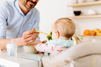 Father feeding baby daughter - p429m1417748 by Sofie Delauw