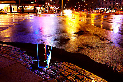 Night view of city with reflections in puddle - p528m713718 by Magnus Ragnvid