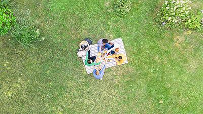 Happy young friends toasting beer bottles in garden - p623m2294747 by Gabriel Sanchez