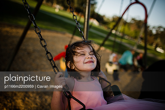 Young girl on swing, closing eyes and smiling - p1166m2200959 by Cavan Images