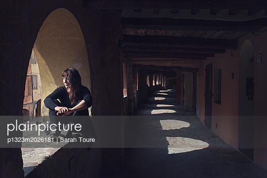 Woman sitting in a window  - p1323m2026181 von Sarah Toure