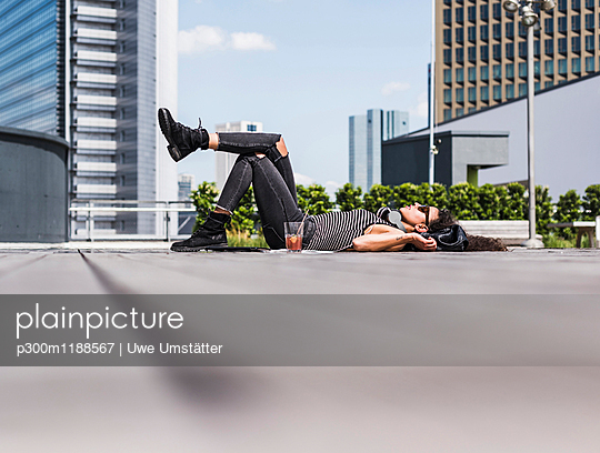 Relaxed young woman wearing headphones lying on the ground