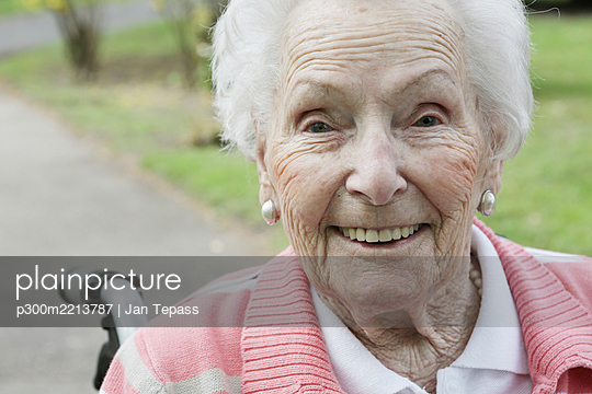 Germany, North Rhine Westphalia, Cologne, Portrait of senior woman sitting on wheelchair, smiling - p300m2213787 by Jan Tepass
