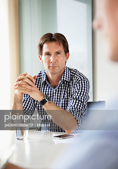 Mature businessman with hands clasped in business meeting