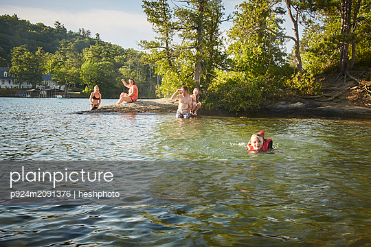 Family swimming in lake - p924m2091376 by heshphoto