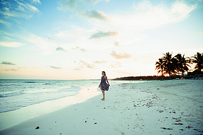 Carefree woman in sun dress on tropical ocean beach Mexico - p1023m2161578 by Paul Bradbury