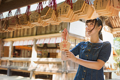 Young woman wearing blue dress looking at wooden fortune telling plaques at Shinto Sakurai Shrine, Fukuoka, Japan. - p1100m1531081 by Mint Images