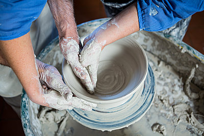 Mid section of male potter assisting female potter - p1315m1199625 by Wavebreak
