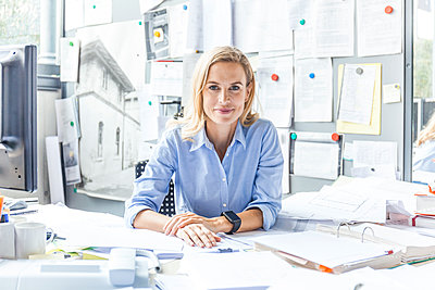 Portrait of confident woman sitting at desk in office surrounded by paperwork - p300m2070865 by Tom Chance