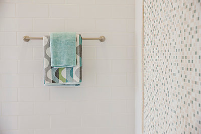 Close-up of towels on rail with tiled and mosaic walls in the bathroom at home - p555m929084f by Eric Hernandez