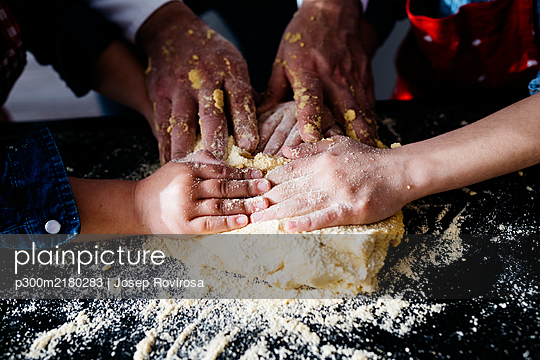Close-up of hands preparing dough in kitchen at home - p300m2180283 by Josep Rovirosa
