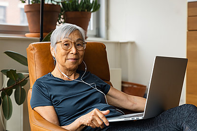 Portrait of senior woman wearing earphones while using laptop at home - p1166m2285595 by Cavan Images