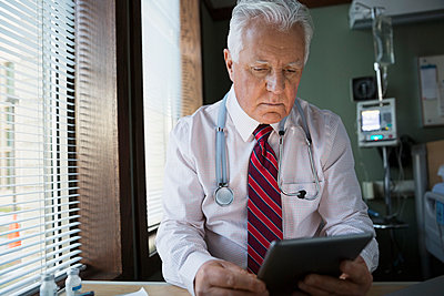 Serious doctor using digital tablet in hospital room - p1192m1016453f by Hero Images