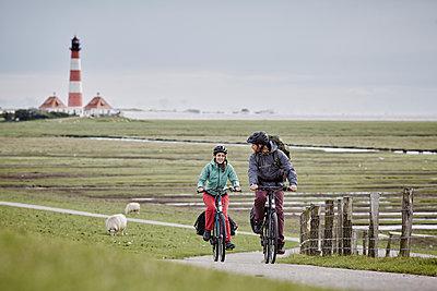 Pärchen mit Trekking-Bikes in Sankt Peter-Ording und am Westerhever Leuchtturm - p300m1416706 von Roger Richter