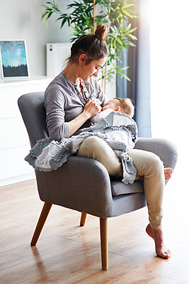Mother sitting on armchair at home breastfeeding her baby - p300m1580944 by gpointstudio