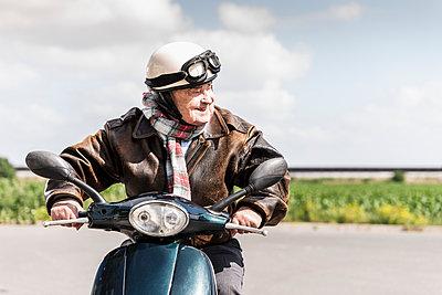 Active senior man speeding on his motor scooter - p300m2030427 von Uwe Umstätter