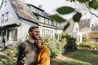 Smiling couple embracing in garden of their home - p300m2166641 by Kniel Synnatzschke