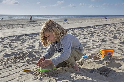 Girl playing at the beach with sand - p896m1478936 by Amaury Miller