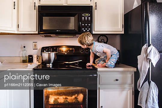 young boy sitting on counter looking at oven timer while cookies bake - p1166m2112355 by Cavan Images