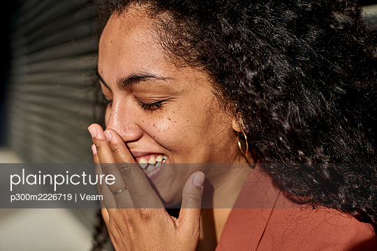 Young woman laughing with eyes closed against shutter on sunny day - p300m2226719 by Veam