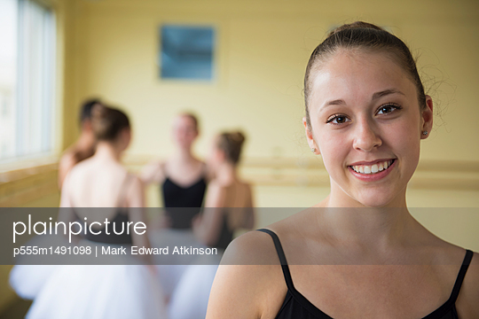 Portrait of girl smiling in ballet studio - p555m1491098 by Mark Edward Atkinson