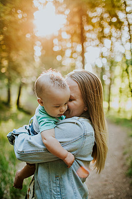 Vertical of happy mother snuggling baby boy outside in forest - p1166m2201880 by Cavan Images