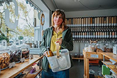 Woman shopping in zero waste shop, Cologne, NRW, Germany - p300m2256205 von Mareen Fischinger