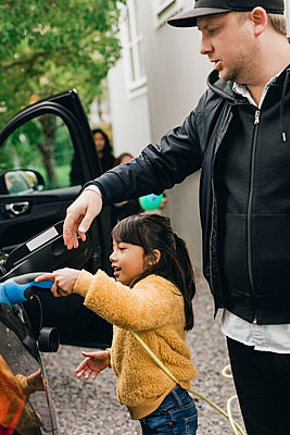Girl helping father in charging car while going for picnic - p426m2195238 by Maskot