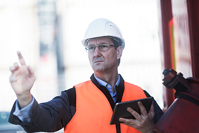 Engineer using digital tablet at port - p429m2164628 by Sigrid Gombert