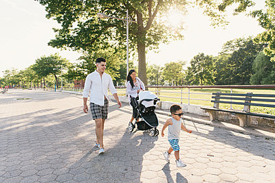Parents walking with pushchair and toddler son at Pelham Bay Park, Bronx, New York, USA - p924m1174907 by Matt Dutile