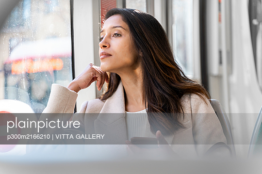 Young woman with smartphone looking out of window in a tram - p300m2166210 by VITTA GALLERY