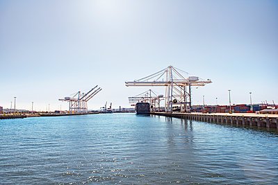 Scenic view of commercial dock at sea against sky - p1166m1142549 by Cavan Images