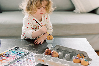 Little toddler girl painting eggs with watercolors for Easter. - p1166m2152341 by Cavan Images