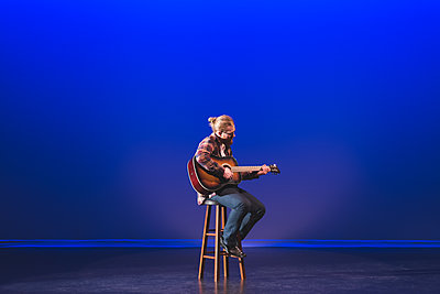 Man playing guitar on stage at theatre - p1315m1566750 by Wavebreak