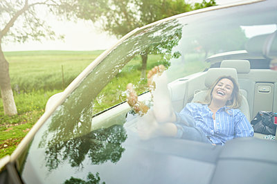 Cheerful woman relaxing in convertible car - p300m2275834 by Kiko Jimenez