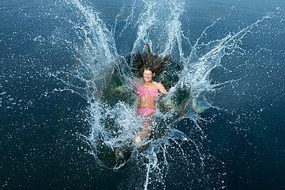 Woman splashing in bathing lake - p427m1195688 by Ralf Mohr