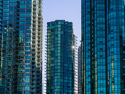 Skyscraper condominiums with glass facade reflecting the blue sky; Vancouver, British Columbia, Canada - p442m2074097 by Keith Levit