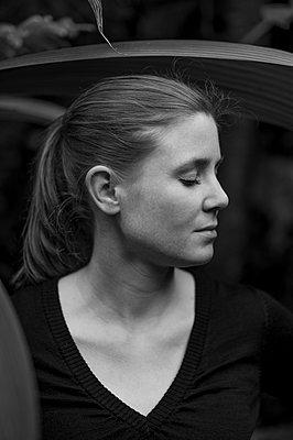 Woman between leaves, Eyes closed - p552m2164139 by Leander Hopf
