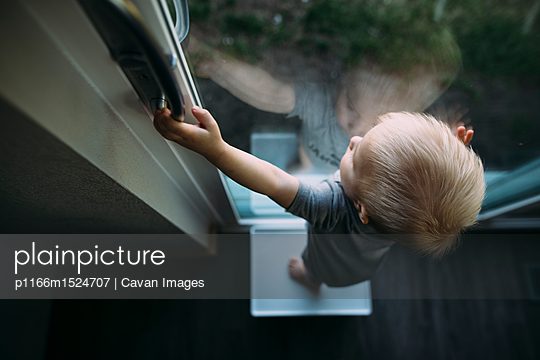 High angle view of baby boy looking through window while standing on stool at home - p1166m1524707 by Cavan Images