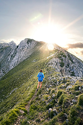 Austria, Tyrol, woman on a hiking trip in the mountains at sunset - p300m2083253 by Florian Küttler