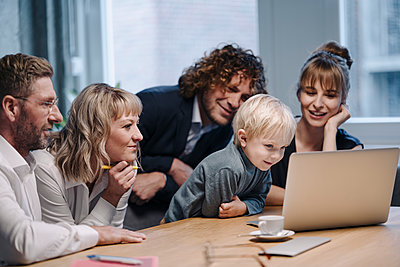 Business team with boy looking at laptop in office - p300m2166776 by Kniel Synnatzschke