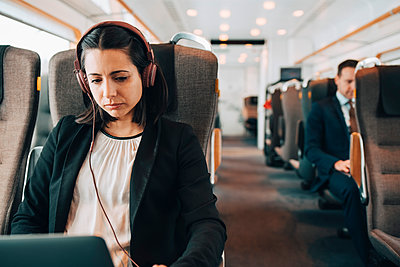 Mid adult businesswoman using headphones and laptop while traveling in train - p426m1580138 by Maskot