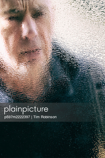 Mans face through textured glass window - p597m2222397 by Tim Robinson