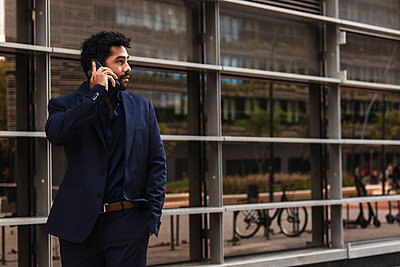 Entrepreneur talking on mobile phone while standing in city - p300m2226448 by NOVELLIMAGE