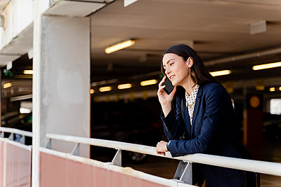 Female entrepreneur talking on smart phone while leaning on railing in parking lot - p300m2287625 by Francesco Morandini