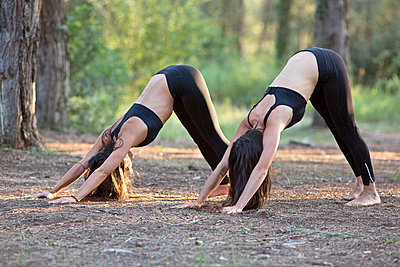 Women Practicing Yoga in a Forest, Downward facing dog Pose - p669m1101775 by Blossom Peaches