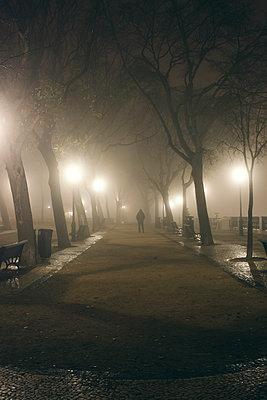Man walking through alley in the dim light of lanterns - p1215m1425640 by Kim Keibel